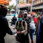 A taxi rank marshal sprays hand sanitiser on a commuter wearing a mask as a preventive measure as she arrives at the Wanderers taxi rank in Johannesburg. Marco Longari/AFP via Getty Images
